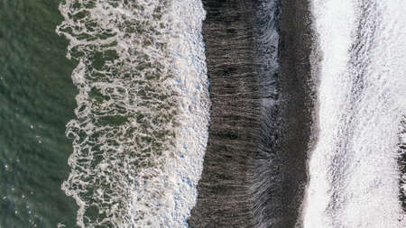 Amazing picturesque view of black sand beach with wave of Reynisfjara in Iceland. Aereal winter landscape view of Reynisfjara from drone. Black sand beach under snow at winter time.