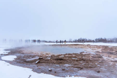 Tourists stand around Strokkur and wait the eruption in Iceland. Eruption of Strokkur a fountain geyser located in the Haukadalur geothermal area, southwest of Iceland. Haukadalur is part of the Golde