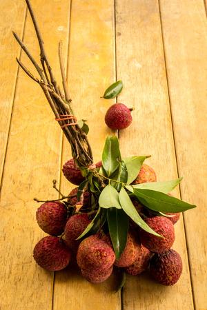 litschi: Lychee, red, floor boards, flooring, background, texture, fruit. Stock Photo