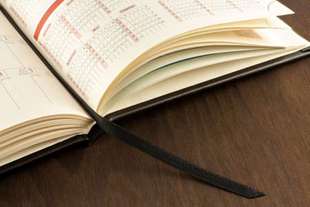 przypominać: Kalendarz na drewnianym tablecalendar, drewniane, stół, data, numer strony, zakładki, brązowym, mianowania, terminarz, imprezy, spotkania, plan, przypomnienie, przypominamy, harmonogram, rok, uwaga, miesiąc