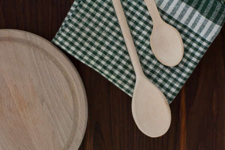 dishcloth: Spoons, dishcloth and bread-board on the wooden background