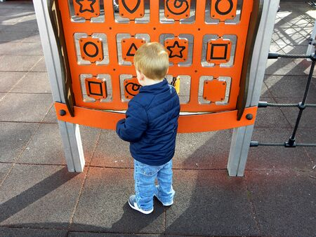 Little boy is playing Tic Tac Toe game in the playground. Leisure time outdoor concept