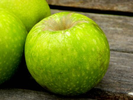 three green apples on a wooden background Stockfoto