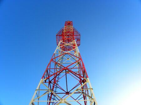 Red and white telecommunications tower and satellite dish of a telecom network against a blue sky Imagens