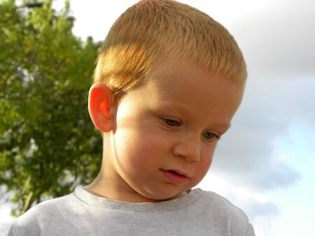 Portrait of a blond boy with gray eyes. Charming three year old boy looked down and is sad. Sad baby Stock fotó