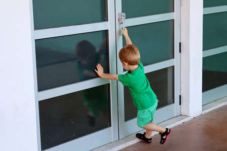A little boy wants to open the door. A three-year-old boy is holding a doorknob. Stock Photo