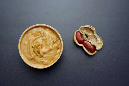 Peanut butter in a round wooden bowl on a gray background.