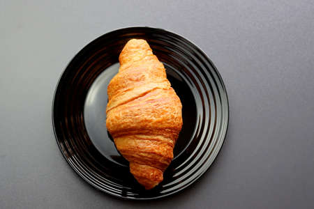 Ruddy croissant on a black plate on a gray background. Crescent-shaped croissant made of puff pastry. Croissant is a popular food in France.