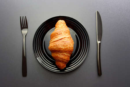 Ruddy croissant on a black plate with a fork and knife on a gray background. Crescent-shaped croissant made from puff pastry. Croissant is a popular dish in France.