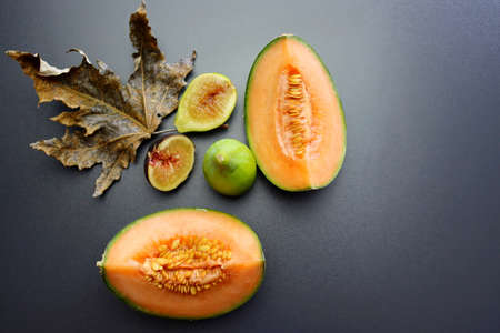 Ripe and juicy cantaloupe melon in a cut and figs on a gray background. Autumn still life with melon and figs. Autumn fruits.