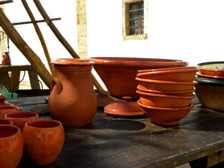 Small clay bowls and a jug on a wooden table. Handmade ceramics 写真素材