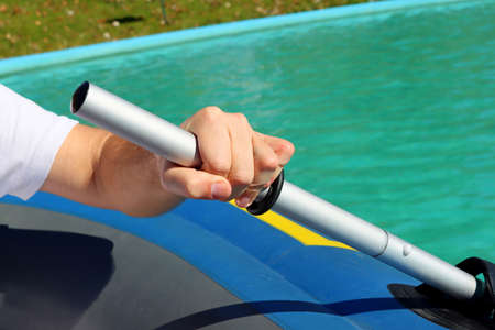 Close-up of a mans hand holding a paddle from a rubber boat against the backdrop of blue water. Banque d'images