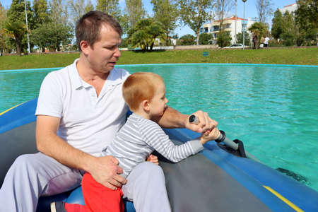 A three-year-old boy sits in a boat with his dad and holds an oar. Little boy learns to row.