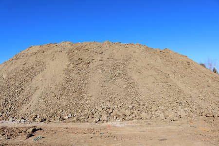 Close-up of a large pile of earth against the blue sky.