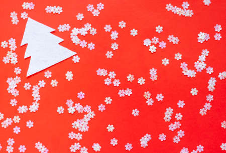 Christmas background shiny white sequins scattered on a bright red background white figure of a Christmas tree Zdjęcie Seryjne