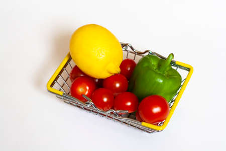 Vegetables in a basket red cherry tomatoes lemon and green bell pepper