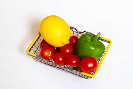 Food in a basket red cherry tomatoes lemon and green bell pepper