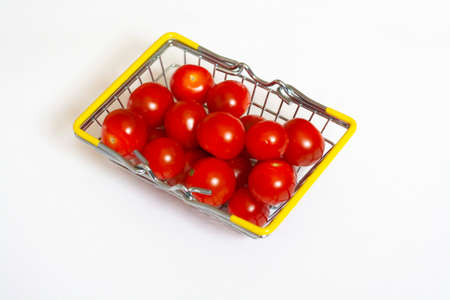 Red cherry tomatoes in a basket isolated on a white background Stockfoto