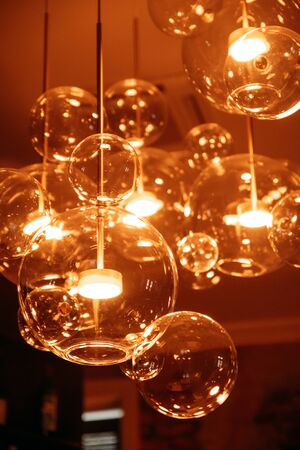 Transparent lamp shade in the form of glass spheres with orange light
