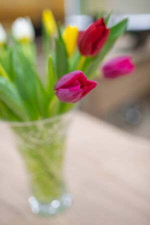 Crystal vase on the table with purple tulips. soft focus, blurred background. close-up