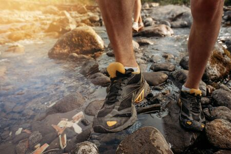 A man in trekking shoes crosses a mountain stream. Close-up on legs