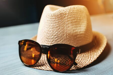 Straw hat with sunglasses on the table. Summer atmosphere
