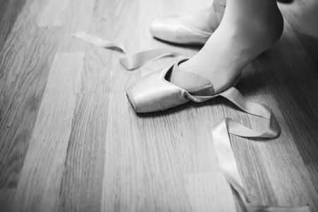 Lacing ballet slippers. Ballerina laces the ribbons of the pointes. BW lifestile photo. close-up of legs
