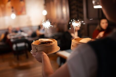 the waiter carries dishes with sparklers. life style, view from the back 스톡 콘텐츠