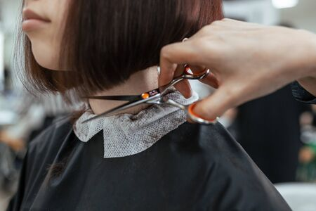 The work of a hairdresser. Hairdresser cut hair of a woman  in a beauty salon. Close-up of hands
