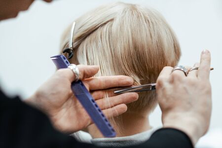 The work of a hairdresser. Hairdresser cut hair of a woman. Close-up of hands and tool Stock Photo