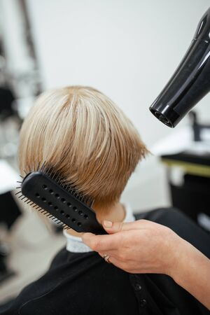 Hairdresser makes hair styling with a hairdryer. Close-up on tools