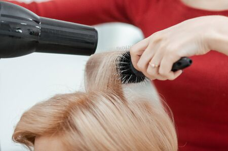 The work of a hairdresser. The master dries the client's hair using brushing. Close-up of hands and tool