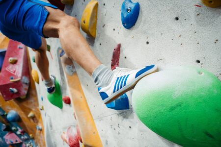 Indoor training climbing wall. Close-up image of male foot on climbing wall