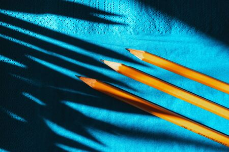 yellow graphite pencils on a blue background, top view. hard shadows