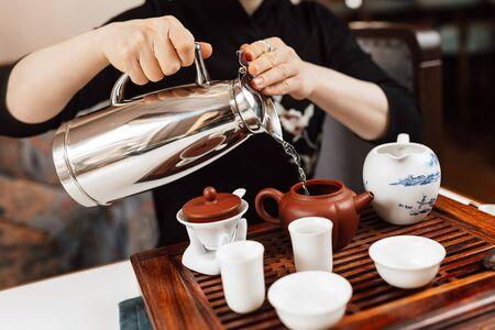 Chinese tea ceremony. Girl pours water into a teapot Zdjęcie Seryjne