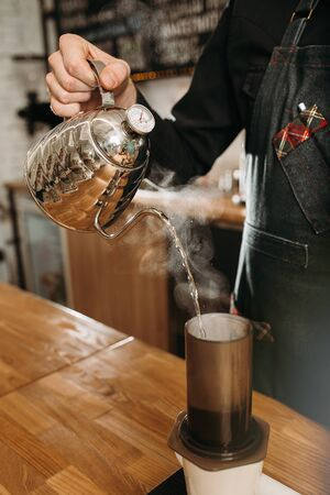 barista preparing coffee in aeropress. barista holding stainless kettle and pouring hot water to aeropress Zdjęcie Seryjne