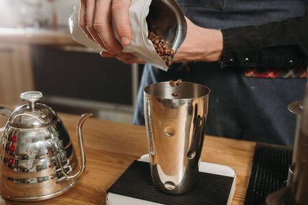 Barista preparing coffee in aeropress. Barista pours coffee grains into a steel glass