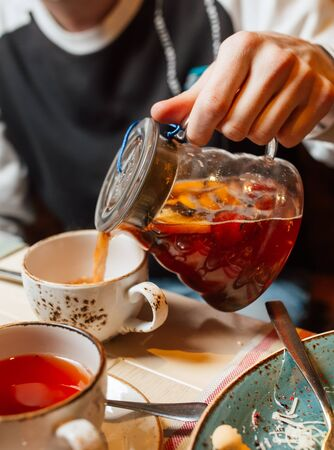 A man pouring a fruit tea with berries from a transparent teapot into a mug, close-up. Lifestyle in a restaurant