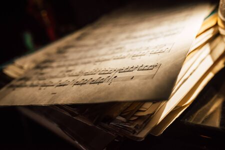 old sheet music in a stack, dimmed lighting