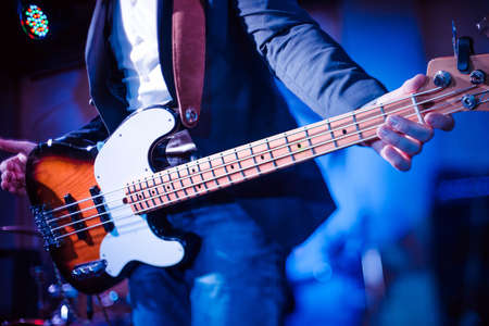 The musician plays the electric bass guitar on stage. Guitar neck close-up on a concert of rock music in the hands of a musician. Fingers on fretboard. Guitar neck close-up on a concert of rock music in the hands of a musician. Fingers on fretboard Фото со стока