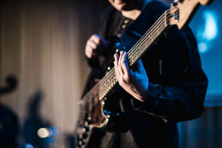The musician plays the electric guitar on stage. Guitar neck close-up on a concert of rock music in the hands of a musician. Fingers on fretboard