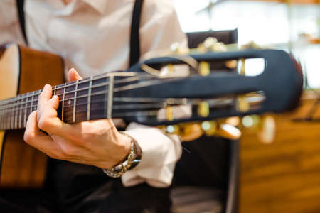 The musician plays the acoustic guitar on stage. Guitar neck close-up in the hands of a musician. Fingers on fretboard