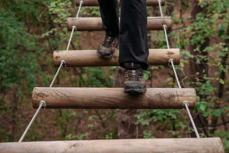 Rope park. A woman in trekking shoes runs a route in a rope park. Close-up of legs