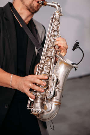 A musician at the event plays the saxophone. Ð¡lose-up of hands and tools Banque d'images