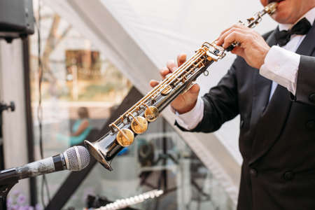 A musician at the event in a frock coat and bow tie plays the saxophone. Ð¡lose-up of hands and tools Stock Photo