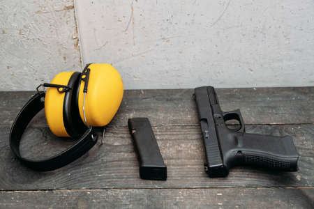 Shooting range. Protective earmuffs and a gun lie on the table 版權商用圖片
