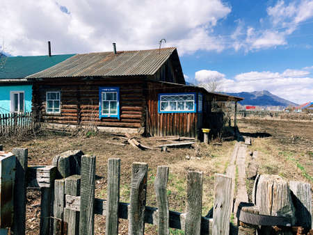 Old wooden house in Russia, Altai. Traditional russian building in a mountain village with blue windows. Landscape in spring time. For blog, articles