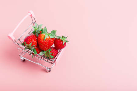 Fresh ripe strawberries in a mini shopping trolley on a pink background. Concept of a supermarket, market, or grocery store. The concept of buying food online on the Internet. copy space, minimalism.