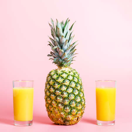 Fresh ripe pineapple and two glasses of pineapple juice on a pink background. hot summer concept. copy space, minimalism. square photo. 免版税图像