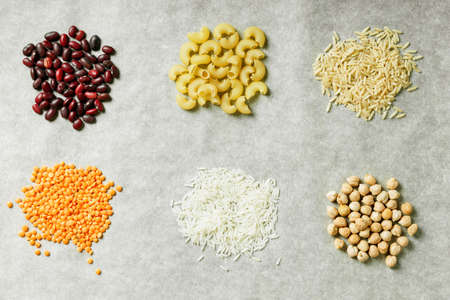Red lentils, white rice, beans, pasta and chickpeas on a grey background. Healthy food concept. Ingredients for cooking.
